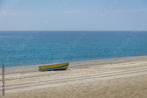 Fotografie, Obraz  Blue and Yellow boat in a Mediterranean beach of Ionian Sea - Bova Marina, Calab