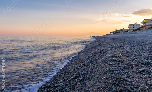 Sunset on a Mediterranean beach of Ionian Sea with Mount Etna Volcano on backgro Canvas Print