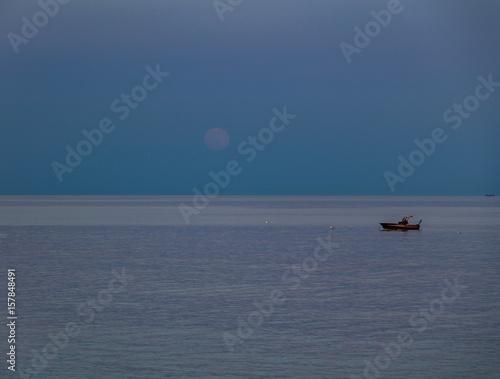 Fototapeta  A boat and a rising moon in a Mediterranean beach of Ionian Sea - Bova Marina, C