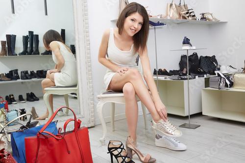 Plakat Młoda kobieta próbuje na nowych butach i torbie w sklepie.