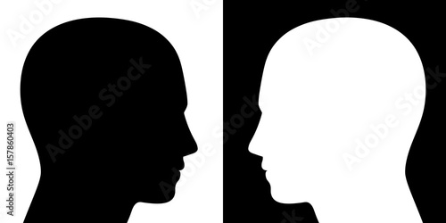 Opposing view - two heads facing each other, one is black on white, the other converse, as a symbol for adverse opinions, contrary ideas, opposite behavior or different beliefs or lifestyle Canvas Print