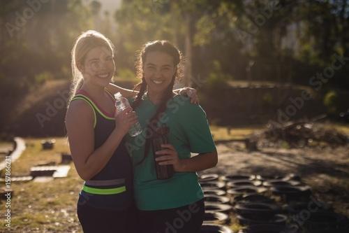 Portrait of happy friends holding water bottle