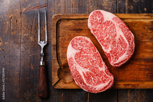 Foto op Canvas Vlees Raw fresh marbled meat Steak Ribeye Black Angus and meat fork on wooden background copy space