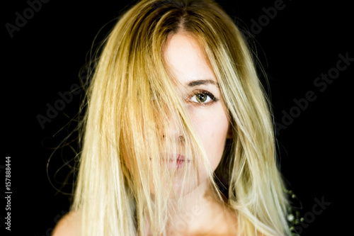 Portrait of a beautiful woman shaking her hair on black background