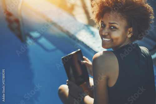 Valokuva  Brazilian young smiling girl with curly african hair is sitting near pool with b