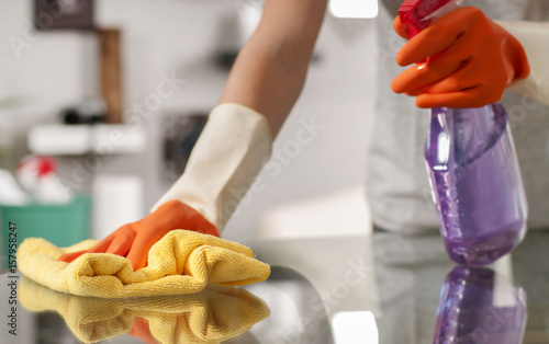 Obraz Woman in gloves cleaning table with spray. - fototapety do salonu