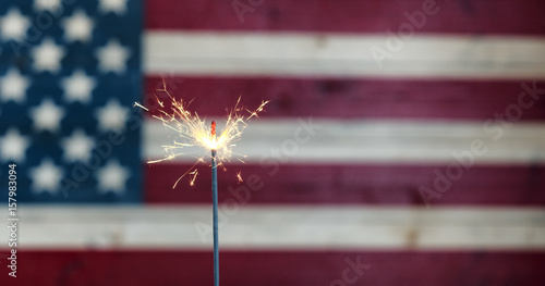 Fotografia  Glowing sparkler with rustic wooden flag of United States of America