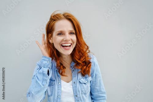 Leinwand Poster lachende frau hält eine hand hinter ihr ohr