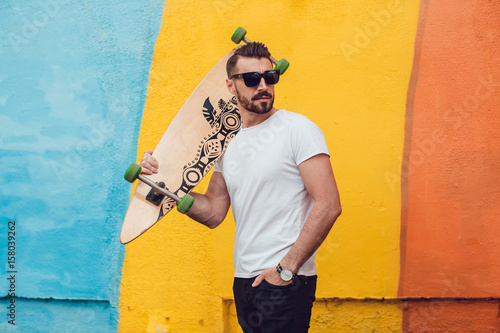 Fotografie, Obraz  Stylish man in sunglasses and with a beard stands on the background of a multi-colored wall with a long board