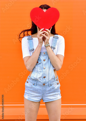 Beautiful woman holding a red heart over orange background Fashion