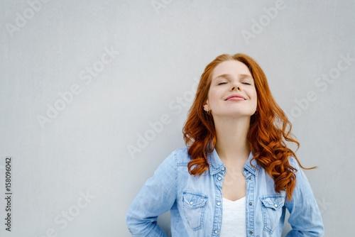 Fotografia  frau lehnt an einer wand und genießt die ruhe mit geschlossenen augen