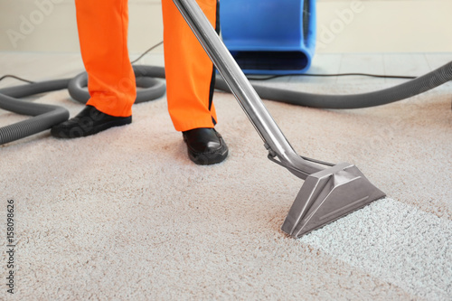 Dry cleaner's employee removing dirt from carpet in flat Canvas Print
