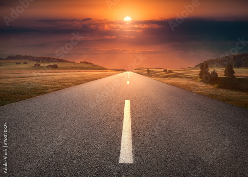 Empty road through mountain scenery at idyllic sunset Poster