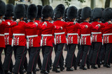 Fototapeta Londyn - Soldiers in classic red coats march along The Mall in London, England in a grand Trooping the Colour spectacle of the Queen's Royal Guard