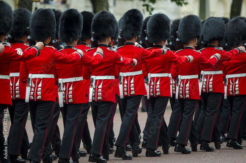 Leinwand Poster Soldiers in classic red coats march along The Mall in London, England in a grand