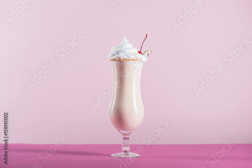 Fotografie, Obraz  fresh milkshake with cream and cherry on top in glass on pink tabletop