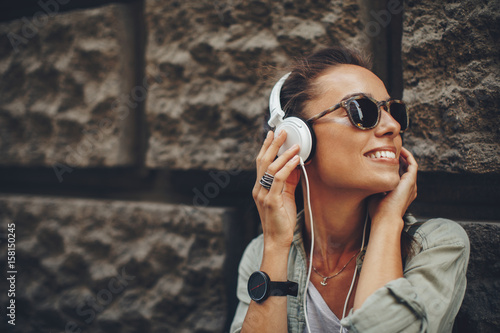 Papiers peints Magasin de musique Happy young woman listening to music via headphones on the street on a sunny day