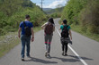 Group of tourists hitching a ride. Travelers travel on the road in mountains go trekking together