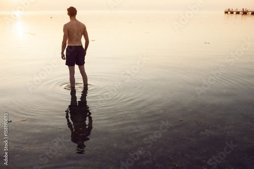 Man in shorts wading in sea at sunset