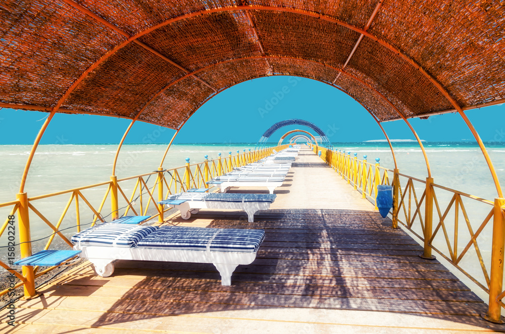 Fototapeta Chaise lounge and parasols on the beach against the blue sky and sea. Egypt, Hurghada