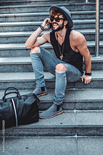 Fototapety, obrazy: Hipster sitting on the stairs while talking on the phone