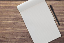 Top View Of Blank Ruled Notepad And Pen Side By Side On Rustic Wooden Table Background Template
