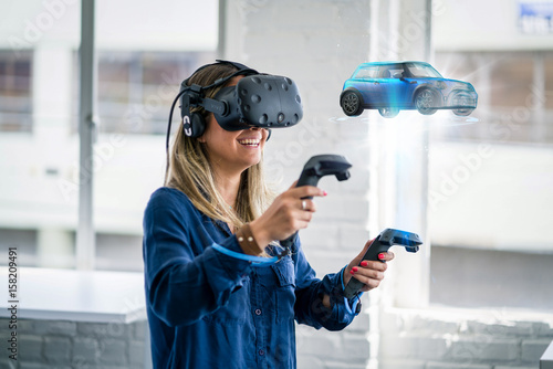 A woman wearing a virtual reality headset looks at a 3D model of a car.