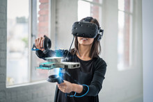 A Woman Wearing A Virtual Reality Headset Interacts With 3D Objects.