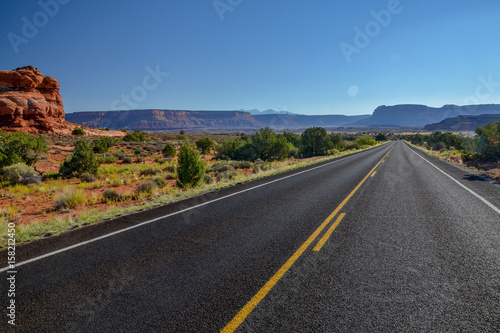 In de dag Route 66 empty country road in grasslands with flat top mountains in the background UT-211 Scenic Highway, Canyonlands National Park, Utah, United States