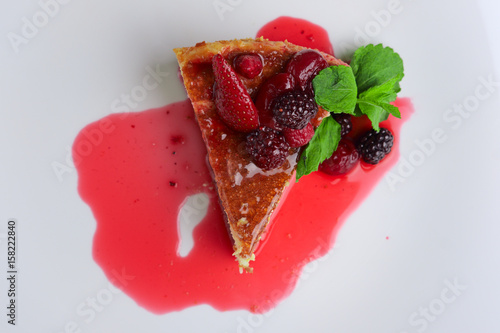 Fotografia, Obraz  Top view of cheesecake with cherry, strawberry and dewberry decorated with syrup