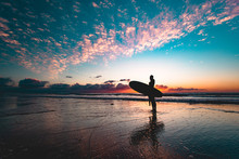 Silhouette Of Female Surfer Holding Surfboard While Standing On Beach