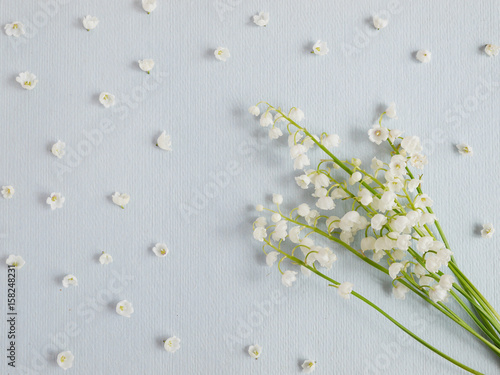Lily of the valley on a blue paper textured background. Pattern of small flowers of the may-lily. Abstract floral background.