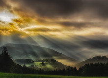 Foggy Glorious Epic Sunrise Over A Rural Idyllic Hilly Countryside,  Fine Art Intense Colored Landscape Scenic Panorama  With Sunrays Over Misty Hills, Fields And Trees