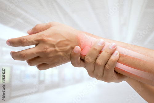 Fotografía  Man massaging painful wrist on a white background. Pain concept