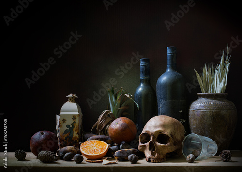 Fotografía Skull and objects expired and dried and rotten fruits on the plank in dim light night / Still life style  and select focus, space for text