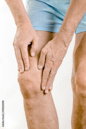 Athlete man massaging a painful  quadriceps and the knee after a sport accident Canvas Print