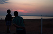Silhouettes of a father and son at sunset at the sea shore