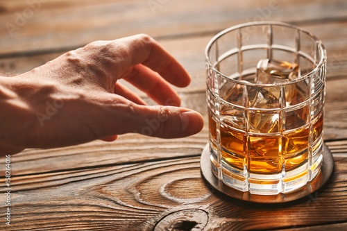 Photo Man's hand reaching to glass of whiskey with ice cubes