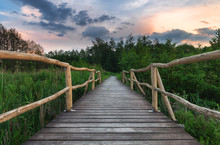 Wooden Path Bridge Over Lake At Sunset After The Storm