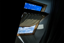 The Window Of The Dark Attic, Open. A View Of A Clear Blue Sky With Clouds.