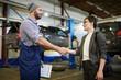 Car repairman and his client handshaking in garage