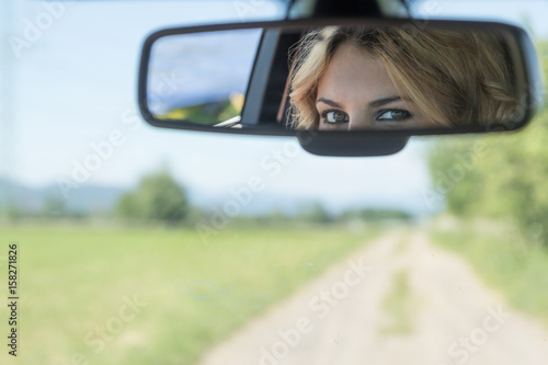 Photo The beautiful eyes of the young driver woman are reflected in the rearview mirror