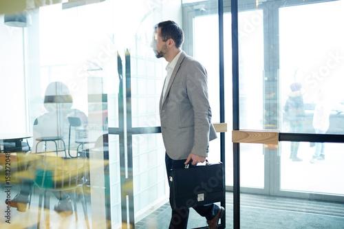 Fotografía  Businessman with briefcase entering cafe