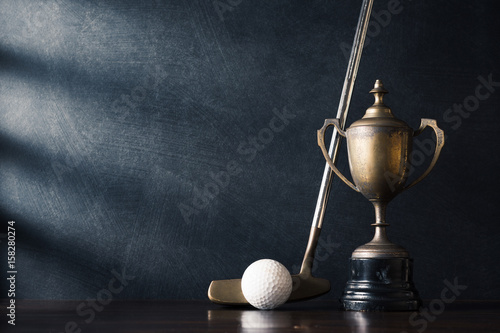 Fotografija  golf club (putter) and ball with old trophy