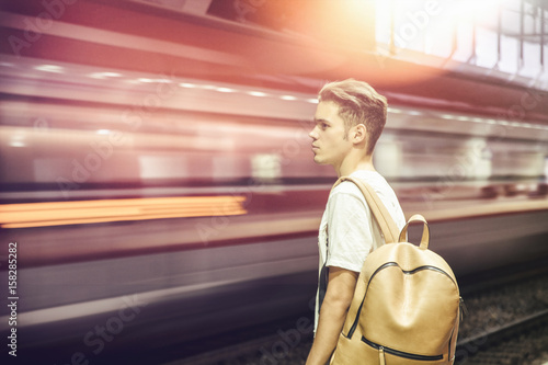 Fotografía  Handsome young male traveler in train station with backpack, looking at blurry t