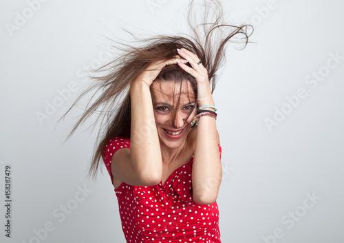 Fotografie, Obraz  Lächelnde Frau mit verwehten Haaren