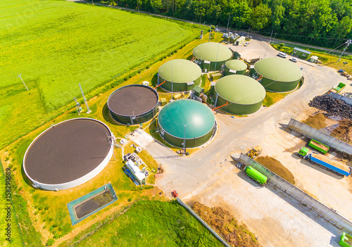 Photo Aerial view over biogas plant and farm in green fields