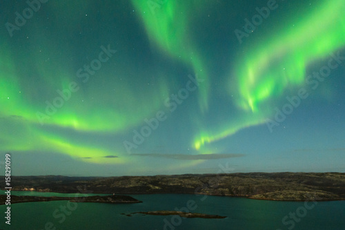 Fotografia, Obraz  The Aurora in the sky above the hills and water on a moonlit night