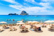 IBIZA ISLAND, SPAIN - MAY 18, 2017: Tourists sunbathing on idyllic beach of Cala d'Hort, Ibiza island, Spain.