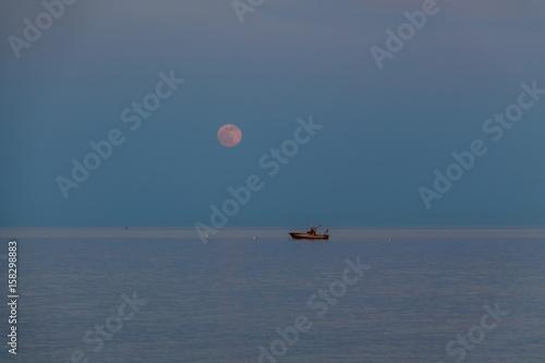Fotografie, Obraz  A boat and a rising moon in a Mediterranean beach of Ionian Sea - Bova Marina, C